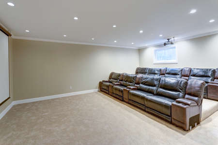 Contemporary basement movie room features a white ceiling accented with a movie projector over black leather chairs.