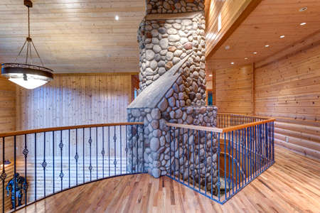 Wedding venue with lovely open floor plan interior. Second floor landing accented with wood paneled walls, ceiling and gorgeous stone trimmed fireplace. Stock Photo