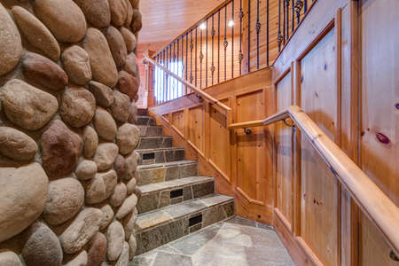 Natural stone staircase leading upstairs features wood paneled walls on one side and stone fireplace on the other.