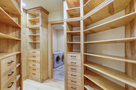 Large walk-in closet lined with built-in drawers, clothes rails and shelving over light wood floor.  Stock Photo