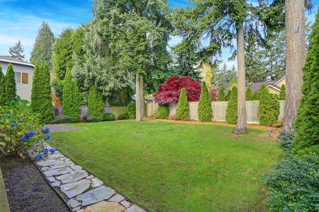 Beautiful Garden Landscape Design with well-maintained lush lawn and garden, stepping stones leading to a patio area.