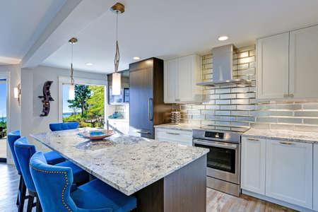 La cuisine bien aménagée comprend un grand îlot de cuisine surmonté d?un comptoir en quartzite gris et flanqué de chaises de salle à manger tuftées de couleur bleue avec une bordure en tête de clou argentée.