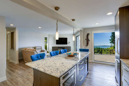 Well appointed kitchen features a large kitchen island topped with a gray quartzite countertop and flanked by blue tufted dining chairs with silver nailhead trim.