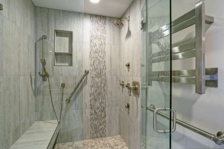 Contemporary bathroom design boasts gorgeous walk-in shower with tiled recessed shelves, built-in bench and accented with glass mosaic tiled vertical stripe.  Stock Photo