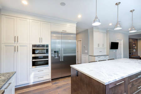 Luxury home interior boasts amazing white kitchen with custom white shaker cabinets, endless marble topped kitchen island and stainless steel appliances over wide planked hardwood floor. Stock Photo