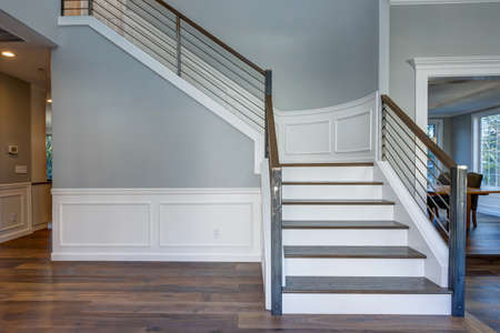 Luxury custom built home interior. Stunning two story entrance foyer design with white wainscoting, grey walls and a white staircase.