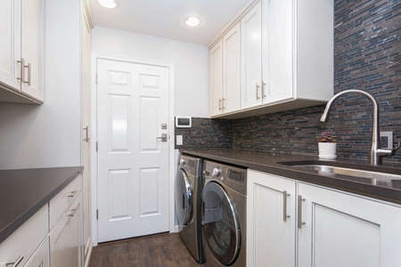 White laundry room boasts white shaker cabinets, brown grey glass tiled backsplash and modern washer and dryer placed under brown counter.
