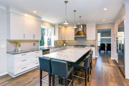 Luxury home interior boasts Beautiful black and white kitchen with custom white shaker cabinets, endless marble topped kitchen island with black leather stools over wide planked hardwood floor.