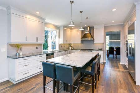 Das luxuriöse Interieur bietet eine wunderschöne schwarz-weiße Küche mit maßgefertigten weißen Shaker-Schränken, eine endlose Kücheninsel mit Marmorplatte und schwarzen Lederhockern auf einem breiten Holzboden.