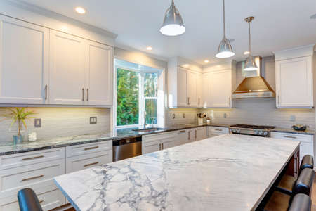 Luxury home interior boasts amazing white kitchen with custom white shaker cabinets, endless marble topped kitchen island and stainless steel appliances over wide planked hardwood floor. Stockfoto