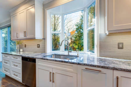 Luxury home interior boasts amazing white kitchen with custom white shaker cabinets topped with granite fitted with a wide stainless steel sink and pull out faucet placed under the window.