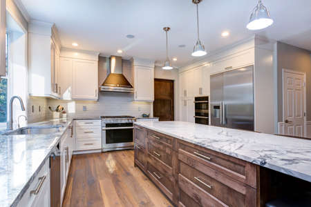 Luxury home interior boasts amazing white kitchen with custom white shaker cabinets, endless marble topped kitchen island with drawers and stainless steel appliances over wide planked hardwood floor.
