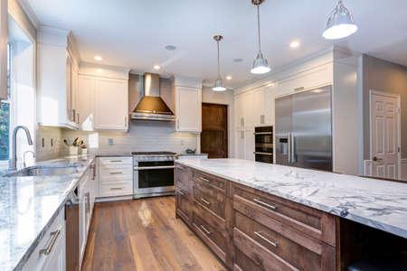 L'intérieur de la maison de luxe comprend une cuisine blanche étonnante avec des armoires à shaker blanches personnalisées, un îlot de cuisine surmonté de marbre sans fin avec tiroirs et appareils électroménagers en acier inoxydable sur un large plancher de bois franc en planches. Banque d'images