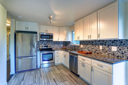L-shape kitchen room design with white cabinets, brown granite countertops, mosaic backsplash, built in stainless steel appliances and wide plank hardwood floor.