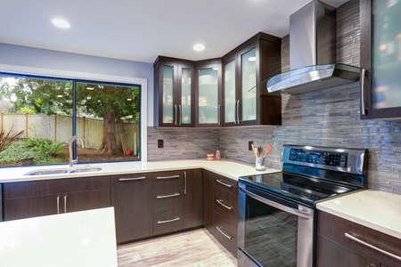 Modernisiertes modernes Interieur des Küchenraums mit weißen Theken und dunklen Holzschränken, die mit luxuriösen Edelstahlgeräten ausgestattet sind.