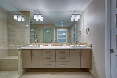Modern refreshing bathroom features a beige dual washstand accented with mosaic backsplash beneath a full length vanity mirror placed next to a walk in shower finished with a glass partition.