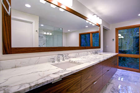 Sleek bathroom features double bathroom cabinet vanity with white gray marble countertop and white rectangle undermount sinks atop marble floor   Stock Photo