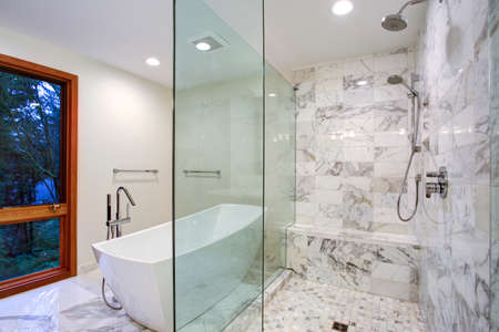 Sleek bathroom features freestanding bathtub paired with floor-mounted faucet atop marble floor placed in front of glass shower accented with rain shower head and gray marble surround.  Stock Photo