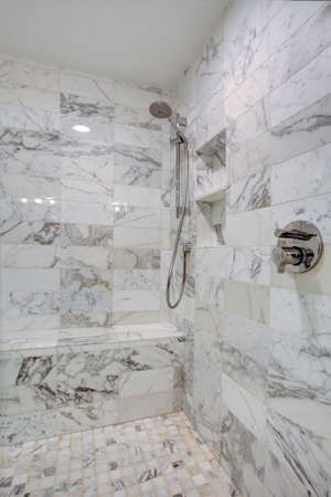 Sleek bathroom features large walk in frameless glass shower with seat,  rain shower heads and gray marble surround. Фото со стока