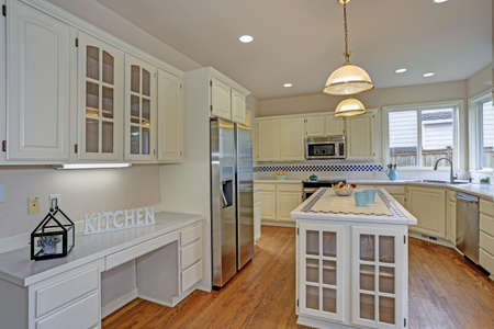 Spacious open floor plan kitchen interior with white shaker cabinets framing new Stainless steel appliances, kitchen island with mosaic tiled counter top.
