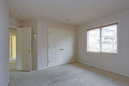 Empty Bedroom With Cream Paint Color Walls, Carpet Flooring And Built In  Closet With