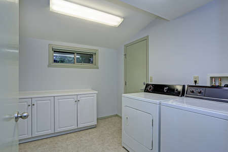 Laundry room with vaulted ceiling, shaker cabinets and white appliances.