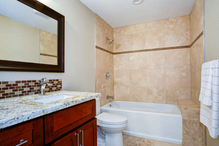 Elegant bathroom with a mahogany stained vanity with a granite countertop, backsplash and undermount sink. White bathtub with beige tile surround accented with brown mini brick tiles.
