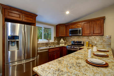 Brown kitchen design with mahogany kitchen cabinets, breakfast bar with stools, granite counter top, brown subway tiles backsplash, stainless steel appliances and vaulted ceiling.