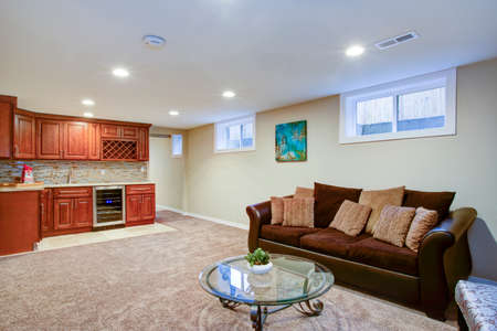 Stunning basement interior boasts a nice wet bar composed of wood shaker cabinets with granite countertop and a mosaic backsplash.