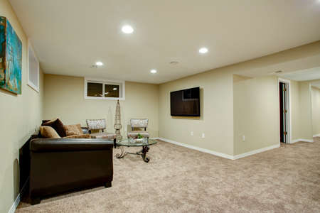 Stunning basement interior with cozy atmosphere, furnished with leather sofa, glass top cocktail table and soft carpet floor.  Stock Photo