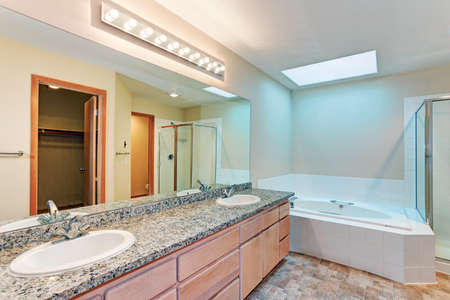 Light and airy bathroom with jetted tub and skylights, large vanity cabinet with two sinks, granite counters and brown vinyl flooring.