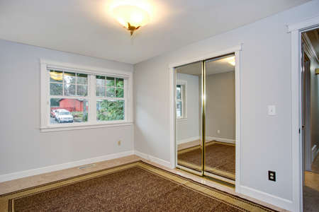 Bright empty room with pure white wall,  mirrored closet doors with a reflection of a brown rug lying on the floor.