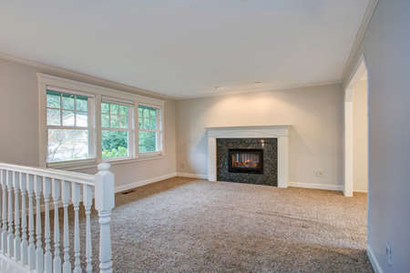 Light open living area with traditional fireplace and carpet floor.