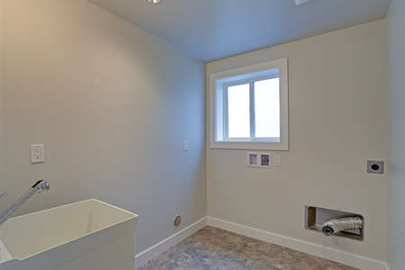 Empty renovated laundry room with white walls. Stock fotó