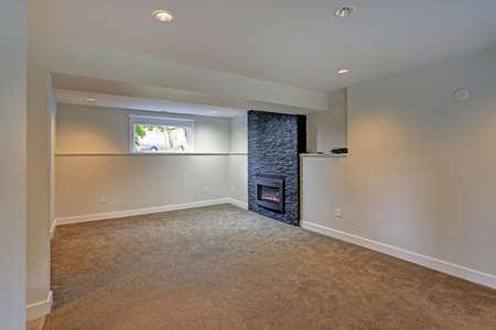Volledig gerenoveerde kelder met witte muren verf kleur, tapijt vloer en zwarte accent open haard. Stockfoto - 95664530