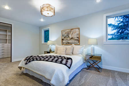 New luxury custom built home features white master bedroom with walk in closet.