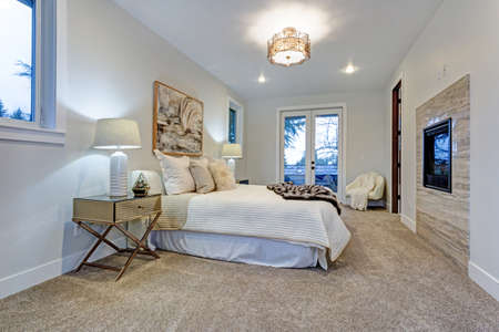 New luxury custom built home with white master bedroom accented with exit to a large patio deck.