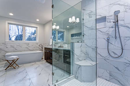 Incredible master bathroom with Carrara marble tile surround, modern glass walk in shower, espresso dual vanity cabinet and a freestanding bathtub.   Stockfoto