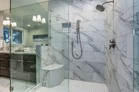 Incredible master bathroom with Carrara marble tile surround, modern glass walk in shower and espresso vanity cabinet.