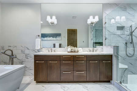 Incredible master bathroom with Carrara marble tile surround, modern glass walk in shower, espresso dual vanity cabinet and a freestanding bathtub.   Foto de archivo