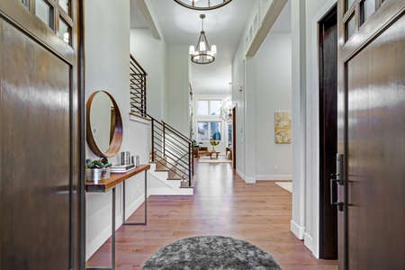 Chic entrance foyer with high ceiling and white walls. New Custom built home interior. Stockfoto
