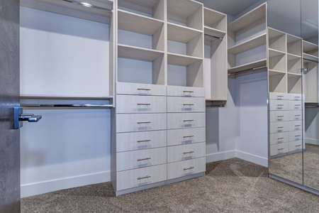 Large walk-in closet lined with built-in drawers, clothes rails and shelving over light brown carpet floor.  Banco de Imagens
