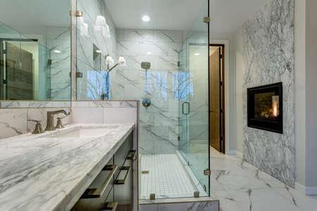 Increíble baño principal con chimenea, revestimiento de baldosas de mármol de Carrara, ducha moderna de vidrio, gabinete de tocador doble espresso y una bañera independiente.