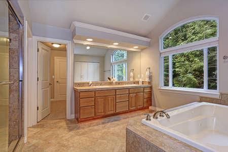 Impresionante baño principal con mueble de tocador doble, gran ventana arqueada, techo abovedado y bañera de hidromasaje de lujo.
