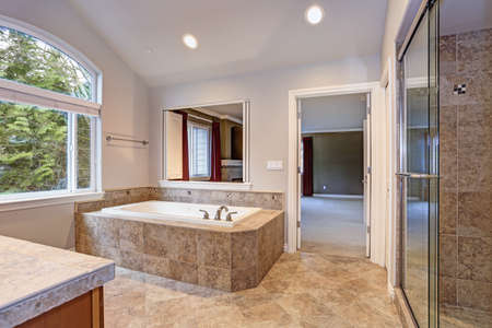 Stunning master bathroom with large arched window, vaulted ceiling and luxury spa tub.