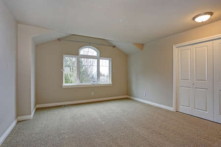 Beige empty room interior with built in closet, carpet floor and large window.