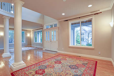 Impressive grand entry with very high ceiling, white columns, a lot of light and polished hardwood floor accented with two colorful rugs.  版權商用圖片