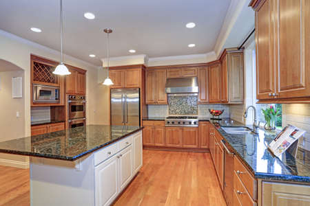 Luxury kitchen with kitchen island, light wood cabinets fitted with Viking appliances.