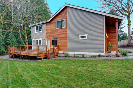 Charming newly renovated home exterior, natural wood siding and grey siding create a beautiful curb appeal. View of a nice walk out deck with wooden handrails. Stock fotó - 96697112