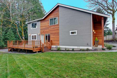 L'extérieur de la maison récemment rénové, le revêtement en bois naturel et le revêtement gris créent un bel attrait. Vue d'une belle terrasse avec balustrades en bois.